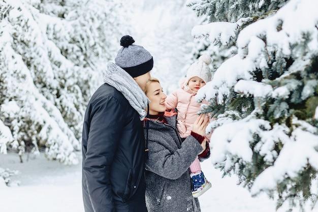 Szczęśliwa Młoda Rodzina Chodzi Z Dzieckiem Na Zimy Ulicie, Mama, Tata, Dziecko Premium Zdjęcia