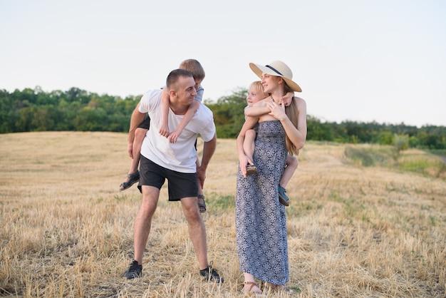 Szczęśliwa młoda rodzina. ojciec, ciężarna matka i dwóch małych synów na plecach. pole pszenicy ukośnej. czas zachodu słońca Premium Zdjęcia