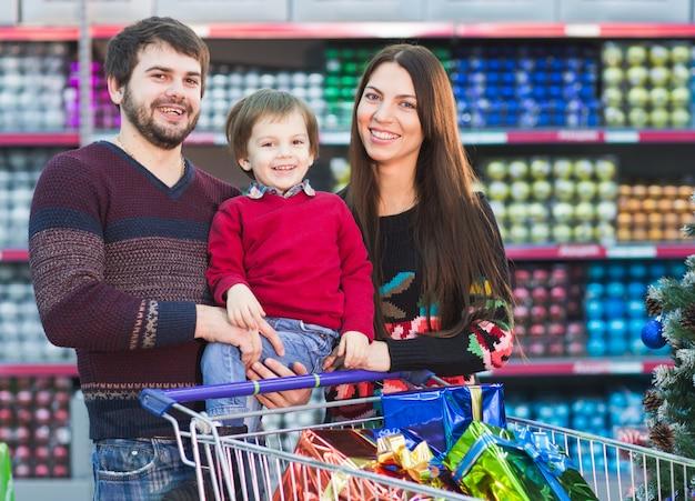 Szczęśliwa Młoda Rodzina W Supermarkecie Wybiera Prezenty Na Choinkę Premium Zdjęcia