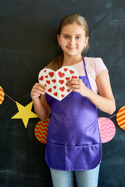 Szczęśliwa Nastoletnia Dziewczyna Trzyma Papierowego Serce Premium Zdjęcia