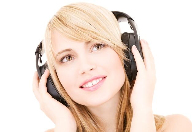 Szczęśliwa Nastoletnia Kobieta W Słuchawkach Na Białym Premium Zdjęcia