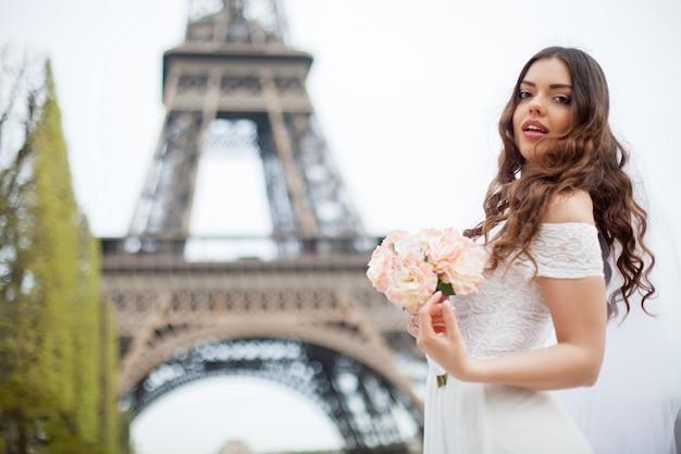 Szczęśliwa panna młoda z bukietem kwiatów pozuje następnie wieża eiffla Premium Zdjęcia