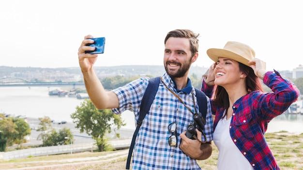 Szczęśliwa para bierze selfie na smartphone przy outdoors Darmowe Zdjęcia