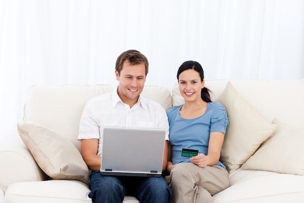 Szczęśliwa Para Kupuje Online Z Laptopem I Kredytową Kartą Na Kanapie Premium Zdjęcia