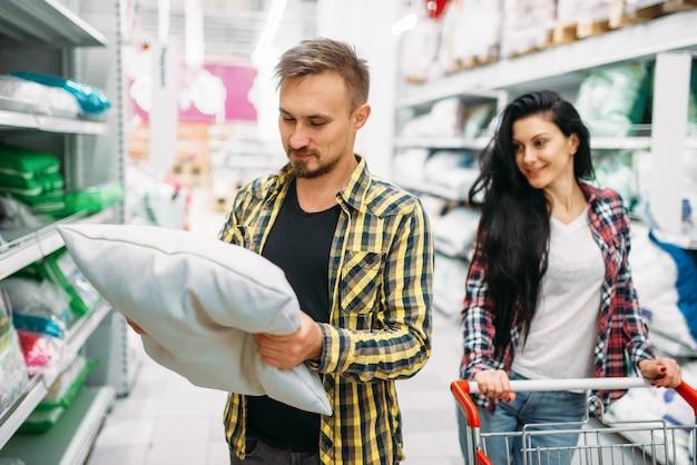 Szczęśliwa Para Kupuje Poduszkę W Supermarkecie. Klienci Płci Męskiej I żeńskiej Na Rodzinne Zakupy. Mężczyzna I Kobieta Kupują Towary Do Domu Premium Zdjęcia