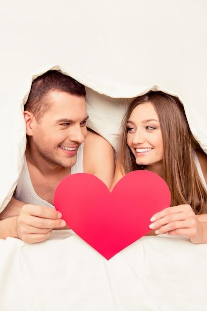 Szczęśliwa Para Leżąc Pod Koc I Trzymając Serce Papieru Ofertowego Premium Zdjęcia