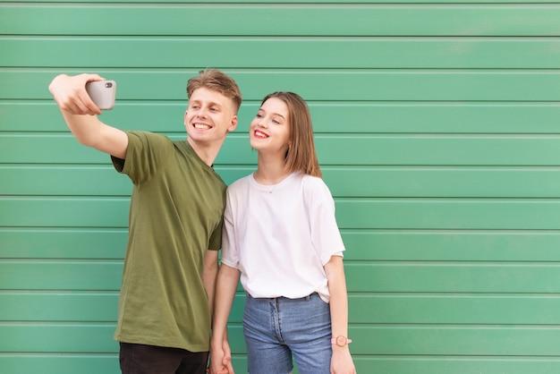 Szczęśliwa Para Młody Mężczyzna I Dziewczyna Wziąć Selfie Na Turkus, Patrząc W Kamerę I Uśmiechając Się Premium Zdjęcia