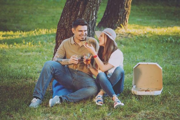Szczęśliwa Para Na Pikniku W Parku. Jeść Pizzę I Pić Piwo Premium Zdjęcia