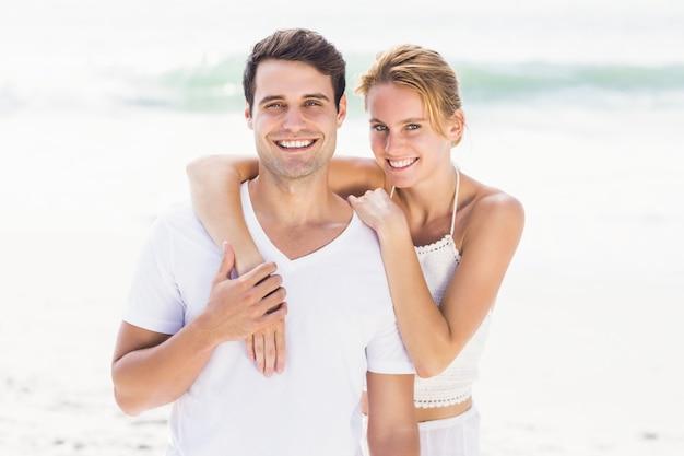 Szczęśliwa para obejmuje each inny na plaży Premium Zdjęcia