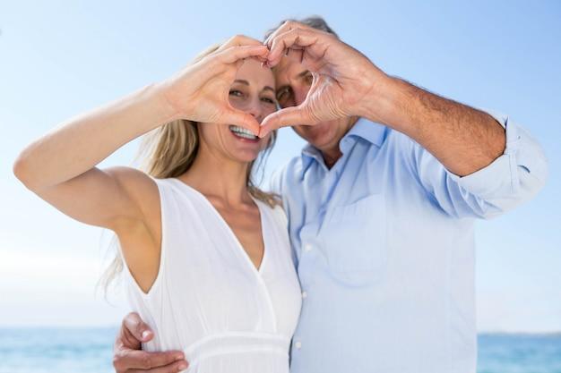 Szczęśliwa Para Ono Uśmiecha Się Przy Kamerą I Robi Kierowemu Kształtowi Z Ich Rękami Premium Zdjęcia
