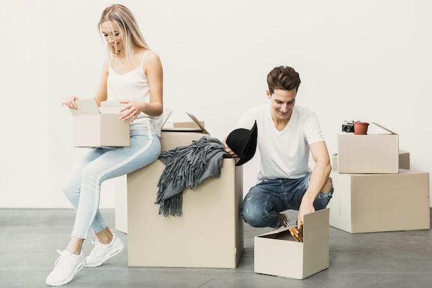 Szczęśliwa para pakowania ubrań w pudełkach Darmowe Zdjęcia