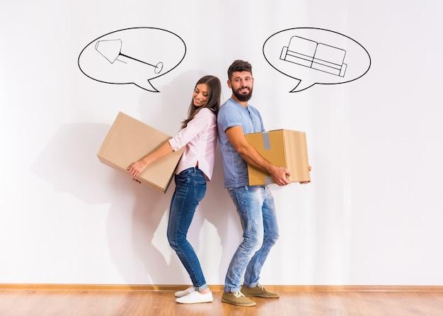Szczęśliwa para przeprowadzka do nowego domu, otwierając pudełka. Premium Zdjęcia