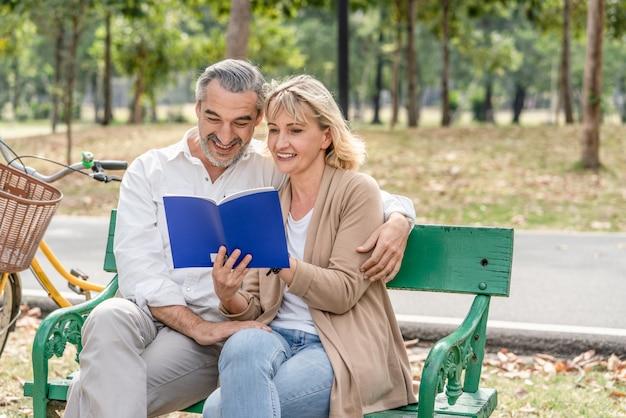 Szczęśliwa Para Senior Czyta Książkę Wpólnie Podczas Gdy Relaksujący I Siedzący Na ławce W Parku Premium Zdjęcia