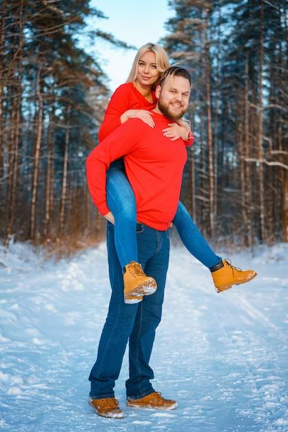 Szczęśliwa para spaceru w śnieżnym lesie Premium Zdjęcia