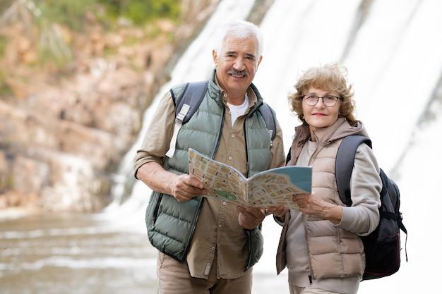 Szczęśliwa Para Starszych Z Plecakami I Mapą Stojącą Przed Kamerą Z Wodospadami W Tyle, Ciesząc Się Podróżą Premium Zdjęcia