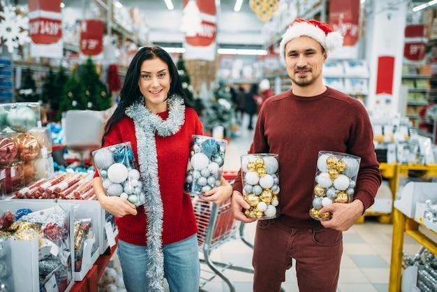 Szczęśliwa Para Trzyma Pudełka Z Zabawkami świątecznymi W Sklepie, Tradycja Rodzinna. Grudniowe Zakupy Artykułów I Dekoracji świątecznych Premium Zdjęcia