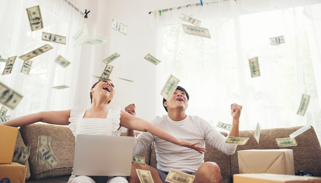 Szczęśliwa para uśmiecha się pomyślnego obsiadanie pod pieniądze deszczem. biznesowa online koncepcja Darmowe Zdjęcia