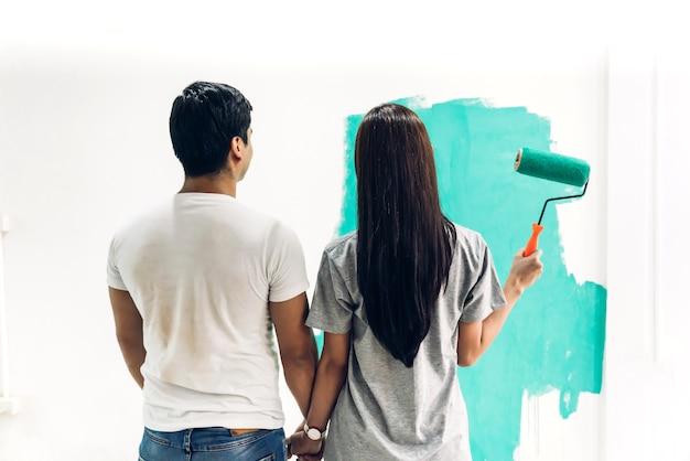 Szczęśliwa Para Używa Wałka Do Malowania I Maluje ściany W Swoim Nowym Domu Premium Zdjęcia