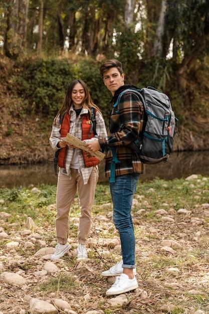 Szczęśliwa Para W Lesie Trzyma Mapę Długo Strzał Darmowe Zdjęcia