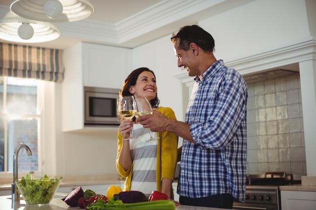 Szczęśliwa Para Wznosi Toast Szkła Wino W Kuchni Premium Zdjęcia