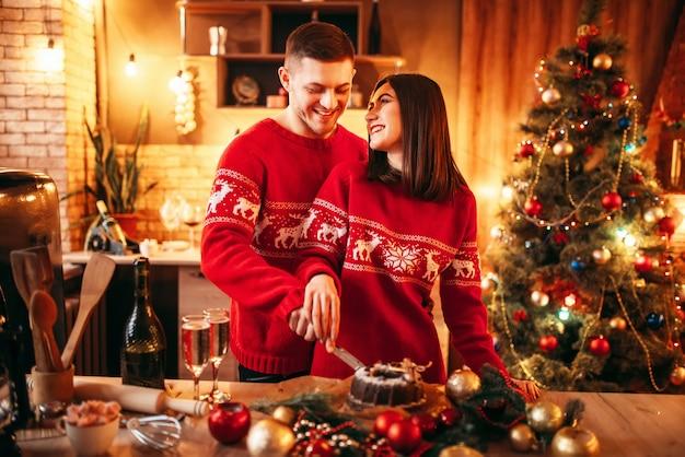 Szczęśliwa Para Zakochanych Smakuje świąteczny Tort, świąteczne Jedzenie. Wspólne świętowanie Bożego Narodzenia, Szczęście Młodej Rodziny Premium Zdjęcia
