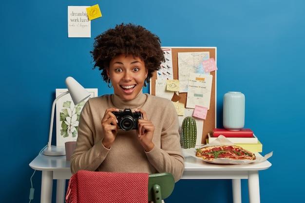 Szczęśliwa Pewna Siebie Kręcona Fotografka Trzyma Aparat Retro, Chętnie Spędza Wolny Czas Na Hobby, Będąc Kreatywną Osobą Darmowe Zdjęcia