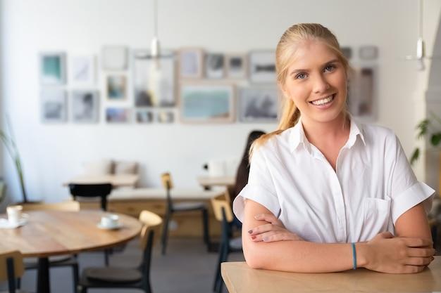 Szczęśliwa Piękna Blondynka W Białej Koszuli, Stojąc W Przestrzeni Coworkingowej, Opierając Się Na Biurku, Pozowanie Darmowe Zdjęcia