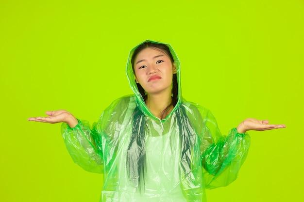 Szczęśliwa piękna dziewczyna, ubrana w zielone ubrania, parasol i płaszcz, deszczowy dzień. Darmowe Zdjęcia