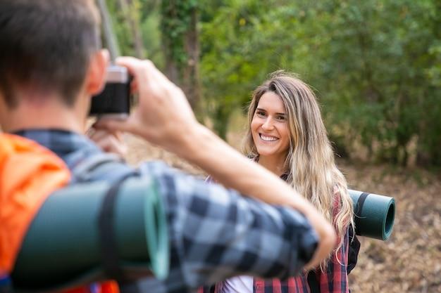 Szczęśliwa Piękna Kobieta Pozuje Do Zdjęć I Stojąc Na Drodze W Lesie. Niewyraźne Facet Robi Zdjęcie Kaukaskiej Uśmiechniętej Podróżniczki. Koncepcja Turystyki Z Plecakiem, Przygody I Wakacji Letnich Darmowe Zdjęcia