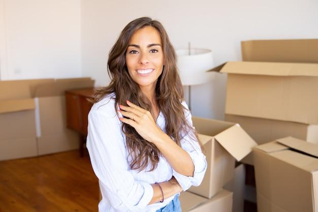 Szczęśliwa Piękna Młoda Kobieta W Nowym Mieszkaniu, Stojąc Przed Stosem Otwartych Kartonów, Patrząc Na Kamery Darmowe Zdjęcia
