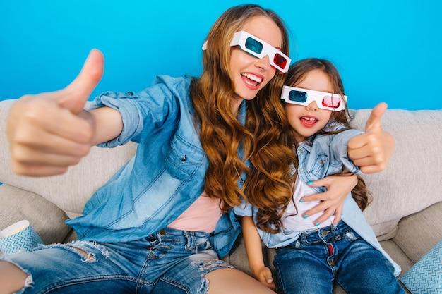 Szczęśliwa Podekscytowana Matka Przytulanie śliczną Córeczkę ładny Na Kanapie Na Niebieskim Tle. Wspólne Oglądanie Filmu 3d W Okularach, Noszenie Dżinsów, Wyrażanie Pozytywnego Nastawienia I Radości Przed Kamerą Darmowe Zdjęcia