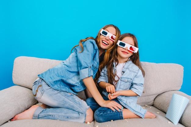 Szczęśliwa Podekscytowana Matka Z ładny ładny Córka Na Kanapie Na Niebieskim Tle. Wspólne Oglądanie Filmu 3d W Okularach, Noszenie Dżinsów, Wyrażanie Pozytywnego Nastawienia I Radości Przed Kamerą Darmowe Zdjęcia