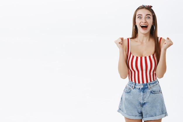 Szczęśliwa Podekscytowana Podekscytowana Kobieta W Stylowych Ubraniach Pin-up Unosząca Zaciśnięte Pięści Z Radości I Wiwatująca Krzycząca Ze Szczęścia Darmowe Zdjęcia