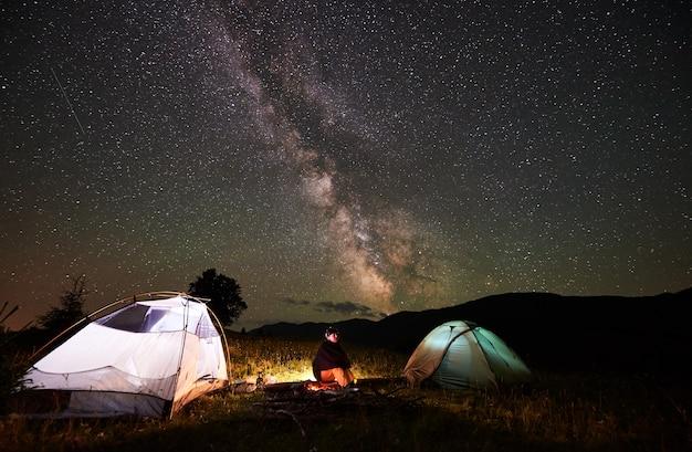 Szczęśliwa Podróżniczka, Ciesząca Się Niesamowitym, Pięknym Gwiaździstym Niebem I Mleczną Drogą Podczas Nocnego Biwakowania W Górach. Kobieta Siedząca Na Kłodzie Obok Ogniska I Dwóch Oświetlonych Namiotów. Premium Zdjęcia