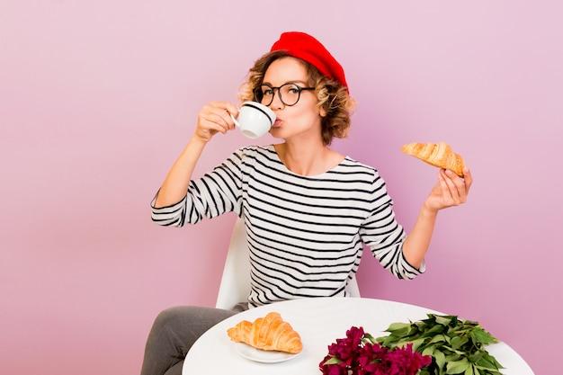 Szczęśliwa Podróżująca Kobieta We Francji, Jedzenie Rogalików Z Kawą, Siedzi Przy Stole Na Różowo. Darmowe Zdjęcia