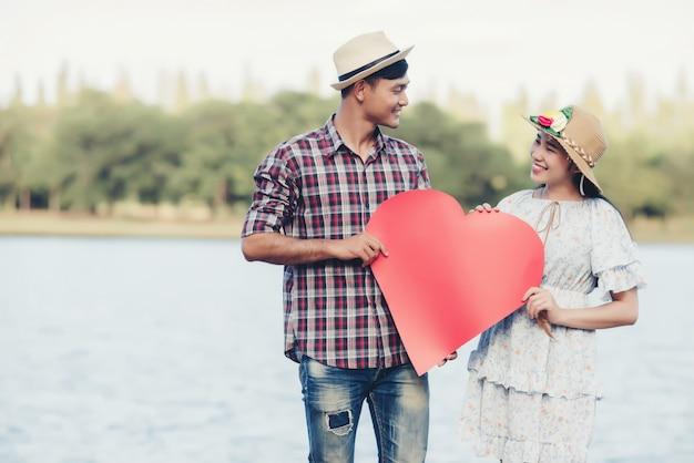 Szczęśliwa potomstwo para trzyma czerwieni papierowych serca Darmowe Zdjęcia
