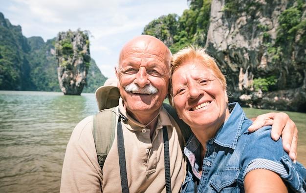 Szczęśliwa Przechodzić Na Emeryturę Starsza Para Bierze Podróży Selfie Wokoło W Tajlandia Premium Zdjęcia