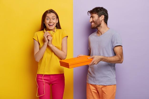 Szczęśliwa Radosna Brunetka Młoda Kobieta Trzyma Się Za Ręce, Ma Na Sobie żółty T Shirt I Różowe Spodnie, Otrzymuje Kartonowe Pudełko Od Chłopaka Darmowe Zdjęcia