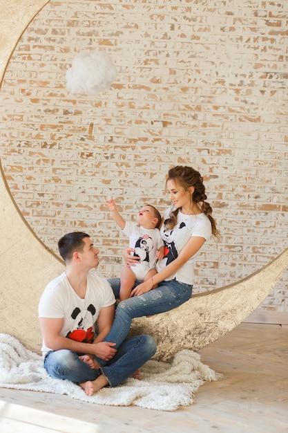 Szczęśliwa rodzina bawić się w minimalistic pracownianym pokoju z ściana z cegieł na tle Darmowe Zdjęcia
