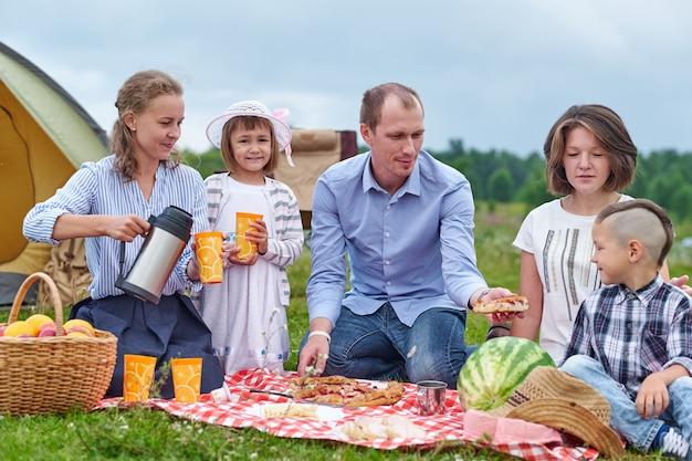 Szczęśliwa Rodzina Ma Pinkin W łące Na Słonecznym Dniu. Rodzina Spożywająca Wakacje Na Kempingu Na Wsi Premium Zdjęcia