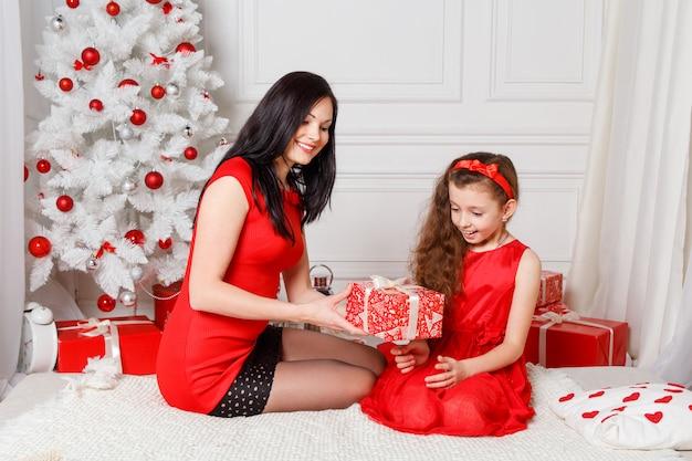 Szczęśliwa rodzina matka i córka dziecko na boże narodzenie eveng z prezentami Premium Zdjęcia