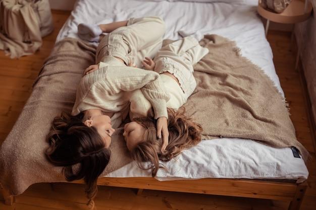 Szczęśliwa Rodzina Matka I Córka Zabawy W Domu Na łóżku Premium Zdjęcia