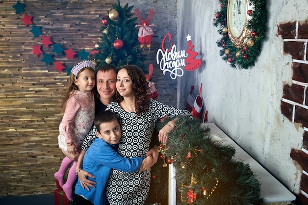 Szczęśliwa Rodzina Na Drzewie Przy Kominku. Mama, Tata I Dwoje Dzieci Na Ferii Zimowych. Wigilia I Sylwester. Premium Zdjęcia