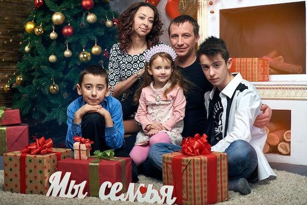 Szczęśliwa Rodzina Na Drzewie Przy Kominku. Mama, Tata I Troje Dzieci Na Ferii Zimowych. Wigilia I Sylwester. Premium Zdjęcia
