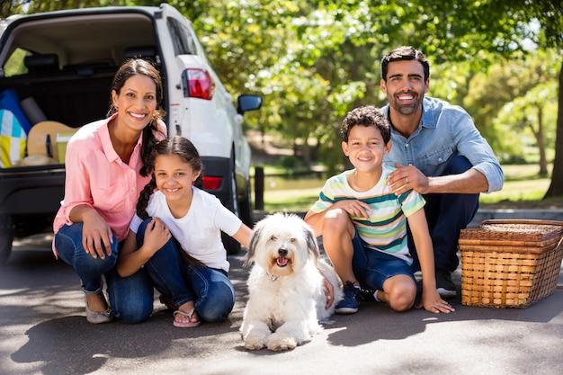 Szczęśliwa Rodzina Na Pikniku Siedzi Obok Samochodu Premium Zdjęcia