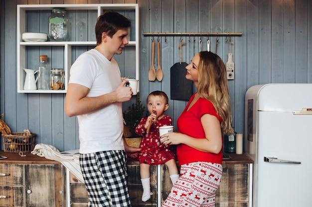 Szczęśliwa Rodzina Na Sobie Piżamy świąteczne Gotowanie Razem Z Małą Córeczką. Premium Zdjęcia