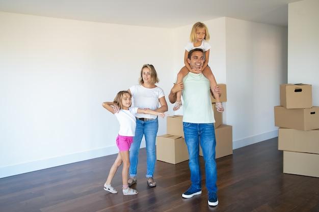 Szczęśliwa Rodzina Para I Dwoje Dzieci, Patrząc Na Swoje Nowe Mieszkanie, Stojąc W Pustym Pokoju Ze Stosami Pudeł Darmowe Zdjęcia