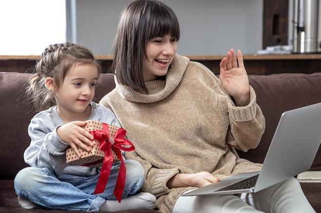 Szczęśliwa Rodzina Patrząc Na Ekran Laptopa Nawiązać Rozmowę Wideo Na Odległość. Uśmiechnięta Matka I Dziewczynka Z Pudełko Rozmawia Z Kamerą Internetową. Darmowe Zdjęcia