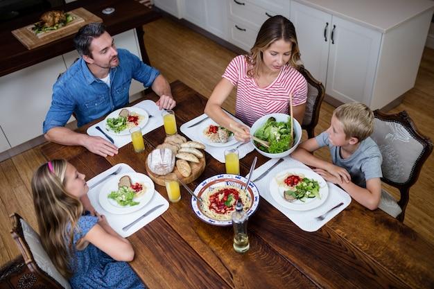Szczęśliwa rodzina rozmawia ze sobą podczas posiłku w kuchni Premium Zdjęcia