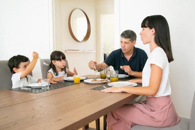 Szczęśliwa Rodzina Siedzi Przy Stole I Razem Jeść Ciastka. Darmowe Zdjęcia